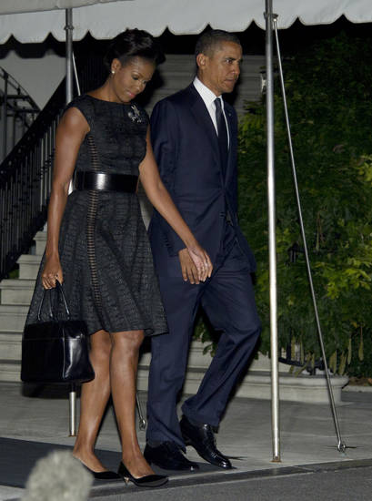 President Barack Obama and first Lady Michelle Obama walk from residence across the South Lawn of the White House to board Marine One, Sunday, Sept. 11, 2011, in Washington, as they travel to New York to take part in the memorial service at ground zero. (AP Photo/Carolyn Kaster)