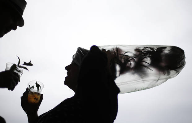 Desirae Masterson, from Indianapolis, Ind., with her hat covered in a plastic bag to protect it from the rain, shares a mint julep with her husband Ray before the running of the 139th Kentucky Derby at Churchill Downs Saturday, May 4, 2013, in Louisville, Ky. (AP Photo/David Goldman)