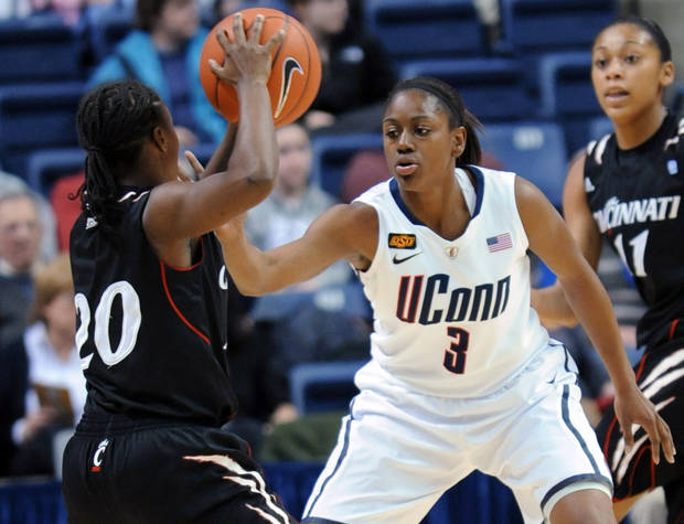 Cincinnati's Bjonee Reaves looks to pass the ball as Connecticut's Tiffany Hayes guards her in the first half of an NCAA college basketball game in Storrs, Conn., Thursday, Jan. 19, 2012. (AP Photo/Bob Child) ORG XMIT: CTRC103