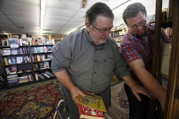 Wayne Stephens (left), owner of Archives Books in Edmond, and Logan Ray organize a case of rare books. The used book store is the second biggest seller on eBay.  <strong>Aliki Dyer - The Oklahoman</strong>