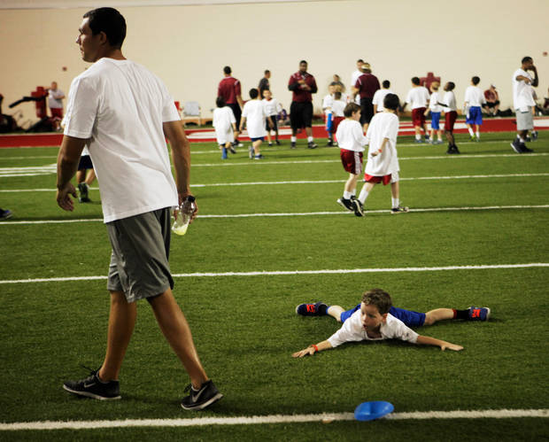 Dylan Sullivan, 7, lies flat on the ground in an attempt to catch a glance from Sam Bradford at Bradford's youth football camp held on campus at the University of Oklahoma on July 14, 2013. Photo by KT KING, The Oklahoman
