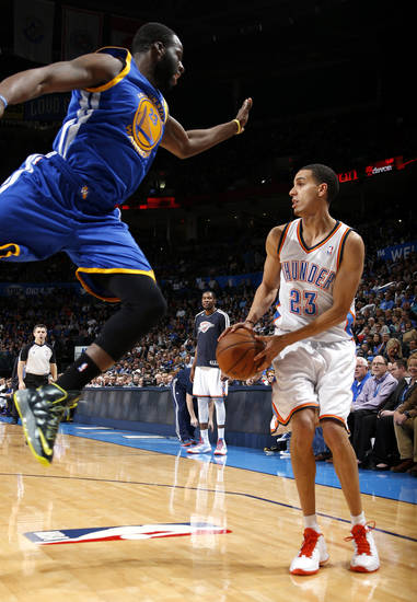 Golden State's Draymond Green (23) leaps towards Oklahoma City's Kevin Martin (23) as he looks to shoot during an NBA basketball game between the Oklahoma City Thunder and the Golden State Warriors at Chesapeake Energy Arena in Oklahoma City, Wednesday, Feb. 6, 2013. Photo by Bryan Terry, The Oklahoman