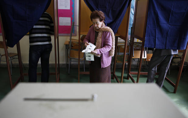 A woman leaves the polling booth as two men are seen in the booths as they vote in the Presidential election in southern port city of Limassol, Cyprus, Sunday, Feb. 17, 2013. Cypriots vote for a new president to guide them through a severe economic crisis that has the country joining other troubled European nations in seeking international rescue money to pull it back from the brink of bankruptcy. (AP Photo/Petros Karadjias)