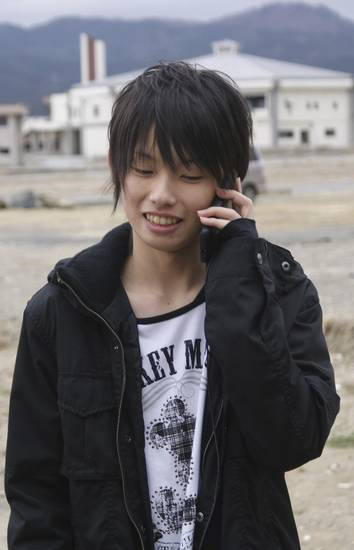   In this April 22, 2012 photo, Misaki Murakami stands where his home, which was washed away by the March 11, 2011 tsunami, once stood, while talking on a mobile phone with David Baxter in Alaska, U.S., in Rikuzentakata, Iwate Prefecture, northern Japan. Baxter found Murakami&#039;s soccer ball, which was lost in last year&#039;s tsunami, on a remote Alaskan island. (AP Photos/Sankei Shimbun, Yoko Watanabe) JAPAN OUT, MANDATORY CREDIT, NO SALES  