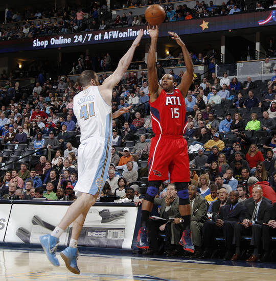 Atlanta Hawks forward Al Horford, right, takes a shot over Denver Nuggets center Kosta Koufos in the first quarter of an NBA basketball game in Denver on Monday, March 4, 2013. (AP Photo/David Zalubowski)