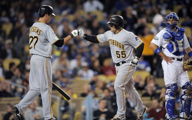 Pittsburgh Pirates' Michael McKenry, center, is congratulated by Jeff Karstens, left, as Los Angeles Dodgers catcher A.J. Ellis watches after McKenry hit a solo home run during the fifth inning of their baseball game, Thursday, April 12, 2012, in Los Angeles. (AP Photo/Mark J. Terrill)