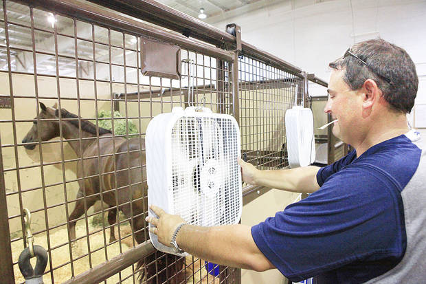 Cody Copland, of Stephenville, Texas, hangs fans on his horses� stalls during 2011�s American Quarter Horse Youth World Championship at State Fair Park. Photo by David McDaniel, The Oklahoman archives
