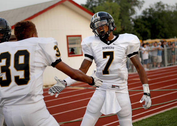 Midwest City's Ronnie Davis, right, celebrates with James Cudjo after Davis returned an interception for a touchdown against Del City during a high school football game in Del City, Okla., Friday, September 2, 2011. Photo by Bryan Terry, The Oklahoman