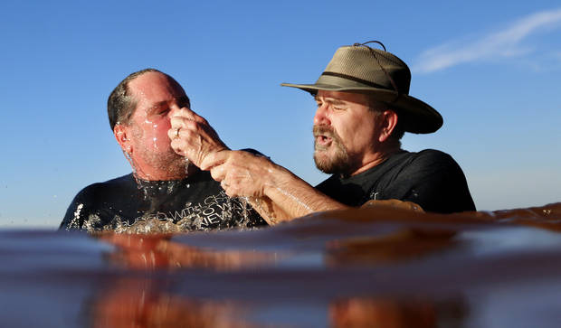 The Rev. Dave Evans with Highland Park Baptist Church baptizes Dr. Brian Johnson   at Clear Bay Point at Lake Thunderbird, Sunday, June 28, 2015, in Norman, Okla. Photo by Sarah Phipps, The Oklahoman