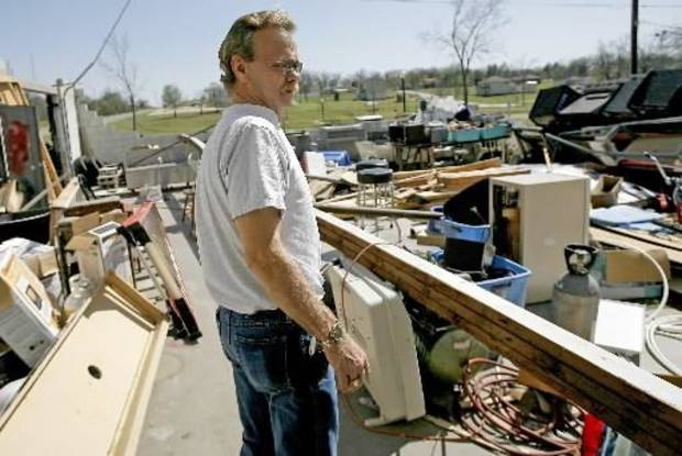 Don Smith looks over damage to his bar in Muldrow, Okla., home, Thursday, April 10, 2008, after severe storms moved through the area Wednesday. Photo by Bryan Terry