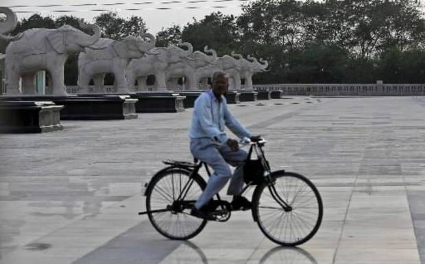 A man rides his cycle past elephant statues, political symbol of the Bahujan Samaj Party (BSP), standing at Ambedkar Park in Noida, on the outskirts of New Delhi, India, Tuesday, March 6, 2012. (AP Photo/Tsering Topgyal)