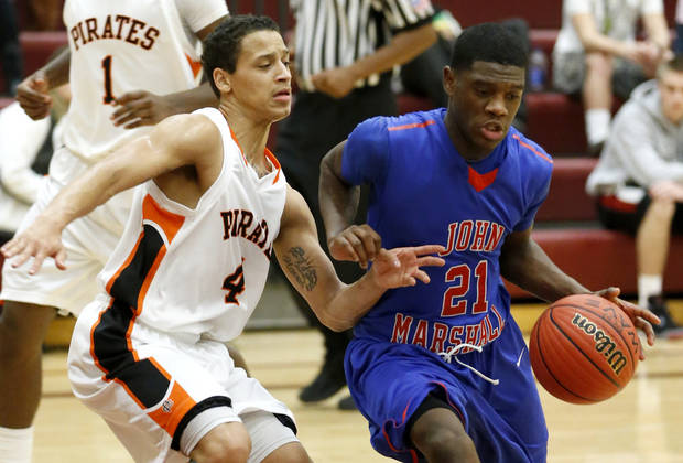 Devion Smith of John Marshall drives past Putnam City&#039;s David Bush during the Putnam City Invitational basketball tournament at Putnam City North High School in Oklahoma City, Thursday, Jan. 10, 2013. Photo by Bryan Terry, The Oklahoman