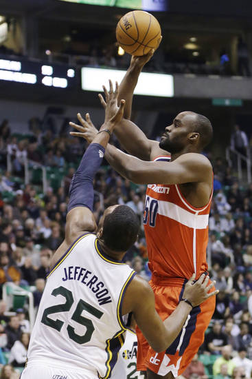 Washington Wizards' Emeka Okafor (50) shoots as Utah Jazz's Al Jefferson (25) defends during the first quarter of an NBA basketball game, Wednesday, Jan. 23, 2013, in Salt Lake City. (AP Photo/Rick Bowmer)