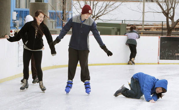Sydney Legaard, left, and Jonathan Barton watch as friend Aubrey Tettleton falls to the ice during the final weekend of skating at the Edmond Outdoor Ice Skating Rink. PHOTOS BY PAUL HELLSTERN, THE OKLAHOMAN