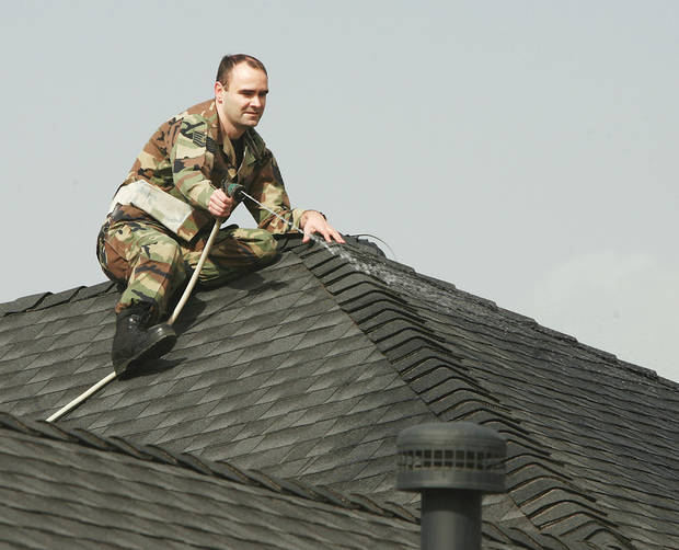 Paul Thurman sits on  top of his house keeping it wet with a garden  hose as wildfires burn Thursday near his home in the Windsong Addition in Midwest City.  Photo by JIM BECKEL,  THE OKLAHOMAN
