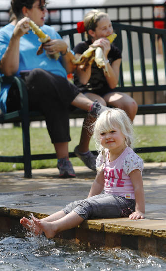 Isabella Lerdall, 3, of Edmond, dangles her toes in the water of the Centennial Waterfall  at the state fair on Monday, Sep. 17, 2012, In background, Kim Teter and daughter, Marissa, 11, of Edmond, eat roasted ears of corn.   Photo by Jim Beckel, The Oklahoman.
