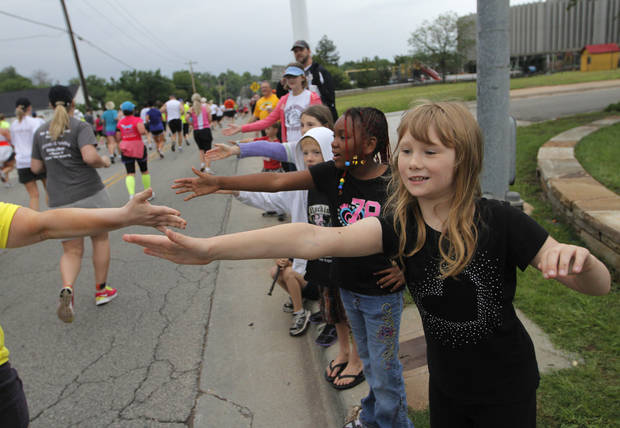 Grace Guttery, 8, and Queeny Sadler, 9, high-five runners during the twelfth annual Oklahoma City Memorial Marathon in Oklahoma City, Sunday, April 29, 2012.  Photo by Garett Fisbeck, For The Oklahoman