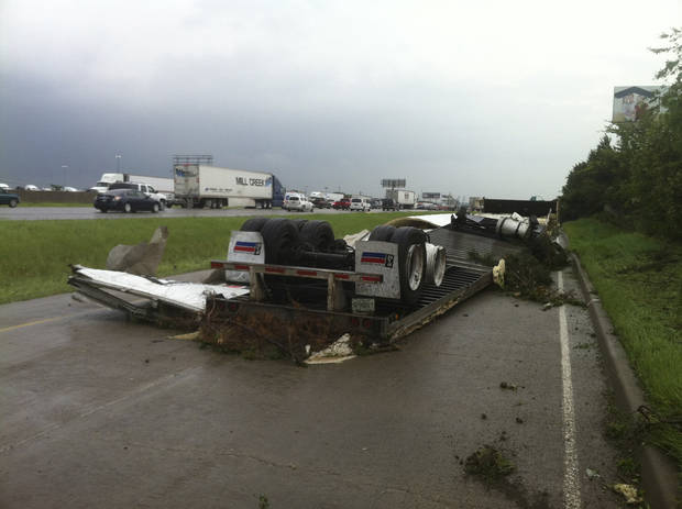 "A trailer is over-turned on I-20 near Bonny view in southern Dallas on Tuesday, April 3, 2012.  Tornadoes tore through the Dallas area on Tuesday, tearing roofs off homes, tossing trucks into the air and leaving flattened tractor trailers strewn along highways and parking lots. The National Weather Service confirmed at least two separate ""large and extremely dangerous"" tornadoes in the Dallas-Fort Worth area. Several other developing twisters were reported as a band of violent storms moved north through the metropolitan area.   (AP Photo/The Dallas Morning News, Nathan Gerry McCarthy)  MANDATORY CREDIT; MAGS OUT; TV OUT; INTERNET OUT; AP MEMBERS ONLY    ORG XMIT: TXDAM108"