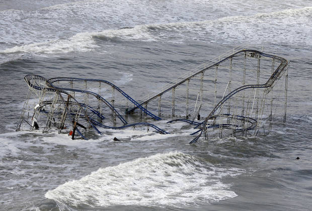 Waves wash over a roller coaster from a Seaside Heights, N.J. amusement park that fell in the Atlantic Ocean during superstorm Sandy on Wednesday, Oct. 31, 2012. New Jersey got the brunt of the massive storm, which made landfall in the state and killed six people. More than 2 million customers were without power as of Wednesday afternoon, down from a peak of 2.7 million. (AP Photo/Mike Groll) ORG XMIT: NJMG108