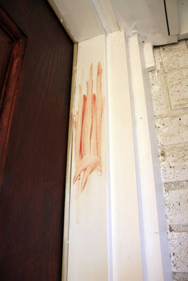 Blood is smeared on the door frame at a home in Richland Hills, Texas, where Brent Troy Bartel is accused of using a box cutter to carve a pentagram in his six-year-old son's back on Wednesday, Dec. 12, 2012. Bartel was charged with aggravated assault with a deadly weapon and was jailed in lieu of $500,000 bond. (AP Photo/Star-Telegram, Bill Miller)