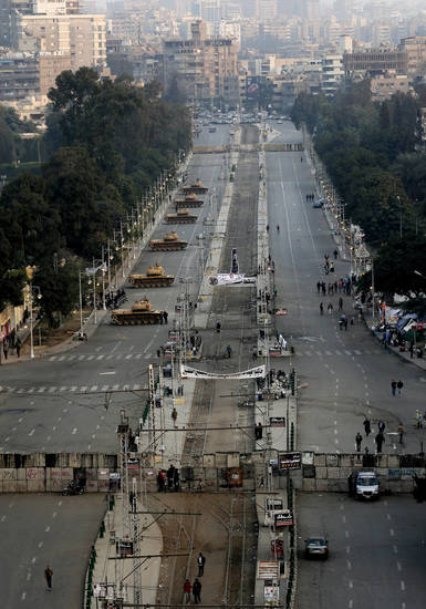 Military tanks deployed in front of the presidential palace in Cairo, Egypt, Sunday, Dec. 16, 2012. Key Egyptian rights groups called Sunday for a repeat of the first round of the constitutional referendum, alleging the vote was marred by widespread violations. Islamists who back the disputed charter claimed they were in the lead with a majority of �yes� votes. (AP Photo/Hassan Ammar)