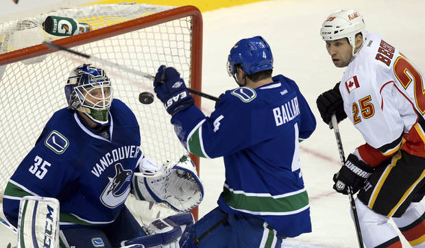 From left, Vancouver Canucks goalie Cory Schneider, Keith Ballard and Calgary Flames' Steve Begin watch the puck after Schneider made a save during the second period of their NHL hockey game, Wednesday, Jan. 23, 2013, in Vancouver, British Columbia. (AP Photo/The Canadian Press, Darryl Dyck)