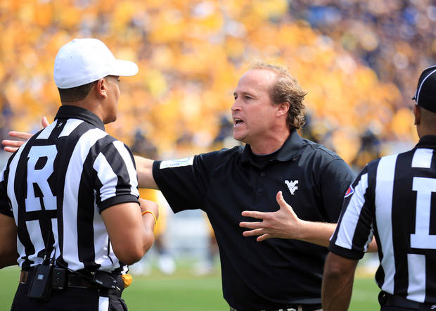 West Virginia coach Dana Holgorsen discuss a call with officals during their NCAA college football game against Baylor in Morgantown, W.Va., Saturday, Sept. 29, 2012. West Virginia defeated Baylor 70-63. (AP Photo/Christopher Jackson)