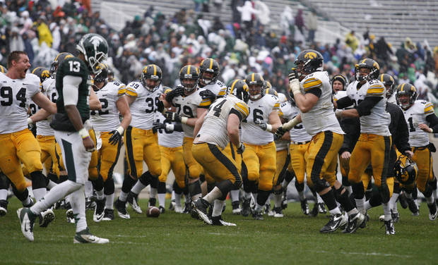 Iowa players celebrate their 19-16 double-overtime win over Michigan State in an NCAA college football game as Michigan State's Bennie Fowler (13) walks off the field, Saturday, Oct. 13, 2012, in East Lansing, Mich. (AP Photo/Al Goldis)