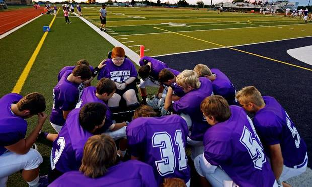 Keegan Erbst prays with the team before a Sequoyah Middle School football game, Thursday, September 27, 2012.