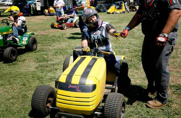 Jessica Shatto bumps fists with her father Jack before a race during the El Reno Grascar Association lawn mower races in El Reno, Saturday, June 6, 2009. Photo by Bryan Terry, The Oklahoman