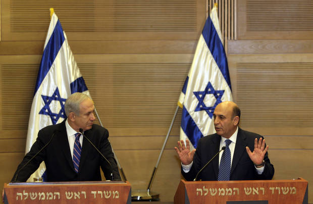 "Israel's Prime Minister Benjamin Netanyahu, left, and Kadima party leader Shaul Mofaz hold a joint press conference announcing the new coalition government, in Jerusalem, Tuesday, May 8, 2012. Netanyahu said Tuesday his new coalition government will promote a ""responsible"" peace process with the Palestinians. (AP Photo/Sebastian Scheiner)"