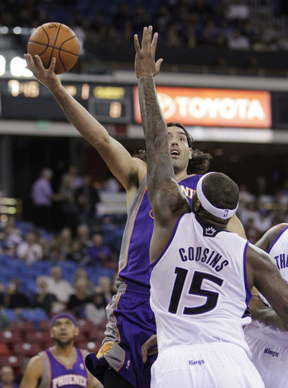 Phoenix Suns forward Luis Scola, of Argentina, shoots over Sacramento Kings center DeMarcus Cousins during the first half of an NBA preseason basketball game in Sacramento, Calif., Wednesday, Oct. 10, 2012. (AP Photo/Rich Pedroncelli)