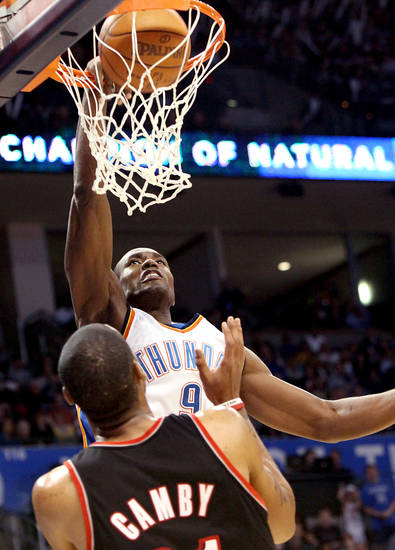 Oklahoma City's Serge Ibaka puts in two points in front of Portland's Marcus Camby during the second half of their NBA basketball game at the Ford Center in Oklahoma City, Okla., on Sunday, March 28, 2010. The Thunder lost to the Trail Blazers. Photo by John Clanton, The Oklahoman