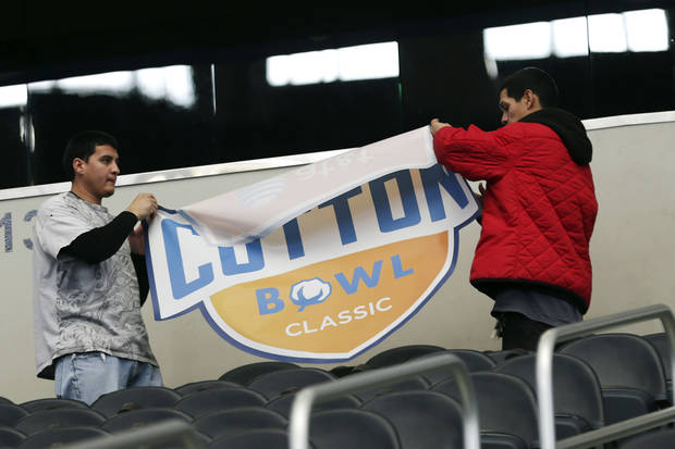 Workers prepare the stands during media day for the Cotton Bowl NCAA college football game at Cowboys Stadium, Sunday, Dec. 30, 2012, in Arlington, Texas. Oklahoma and Texas A&M are scheduled to play each other on Jan. 4, 2013. (AP Photo/LM Otero) ORG XMIT: TXMO109