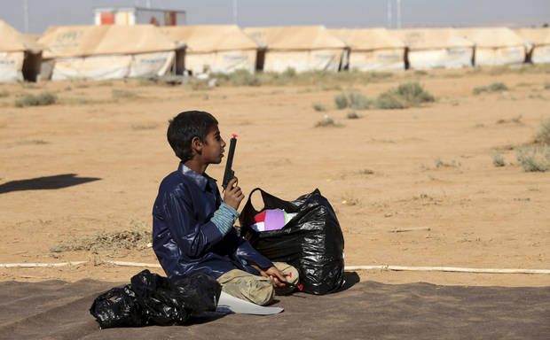 A Syrian refugee plays with a new toy suction dart gun, one of the gifts he received from charities, on the first day of the Eid al-Fitr holiday, at Zaatari Refugee Camp in Mafraq, Jordan, Sunday, Aug. 19, 2012. Muslims around the world celebrate Eid al-Fitr, marking the end of Ramadan, the Muslim calendar's ninth and holiest month during which followers are required to abstain from food and drink from dawn to dusk. (AP Photo/Mohammad Hannon)