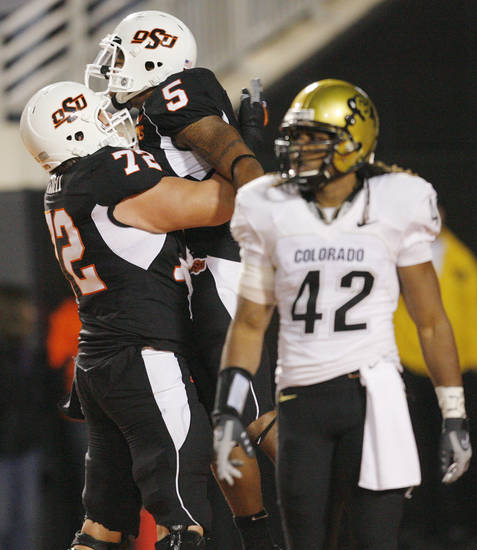OSU's Andrew Mitchell (72) and Keith Toston (5) celebrate a touchdown catch by Toston in the fourth quarter as Colorado's Benjamin Burney (42) walks away during the college football game between Oklahoma State University (OSU) and the University of Colorado (CU) at Boone Pickens Stadium in Stillwater, Okla., Thursday, Nov. 19, 2009. OSU won, 31-28. Photo by Nate Billings, The Oklahoman