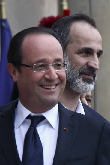French President Francois Hollande, left, smiles as he welcomes head of the new Syrian National Coalition for Opposition and Revolutionary Forces Mouaz al-Khatib, right, prior to a meeting, at the Elysee Palace, in Paris, Saturday, Nov. 17, 2012. France has taken a leading role among Western countries in supporting Syria's rebels. On Tuesday, it became the first Western nation to formally recognize Syria's newly formed opposition coalition as the sole legitimate representative of the Syrian people. (AP Photo/Thibault Camus)