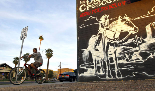 A cyclist pedals on Roosevelt Street along the Roosevelt Row neighborhood Tuesday, Nov. 27, 2012, in Phoenix.  The neighborhood is home to First Friday Art Walk, a Phoenix tradition since 1994, promoting local artists and shops.(AP Photo/Ross D. Franklin)