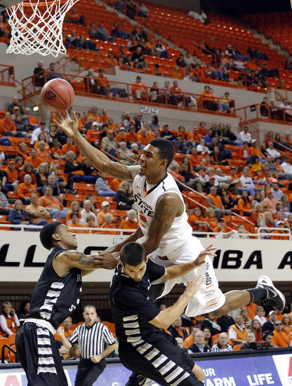 Oklahoma State's Le'Bryan Nash (2) is fouled by Portland State's Dre Winston Jr. (3) and Portland State's Michael Harthun (4) during the college basketball game between Oklahoma State University and Portland State, Sunday,Nov. 25, 2012. Photo by Sarah Phipps, The Oklahoman