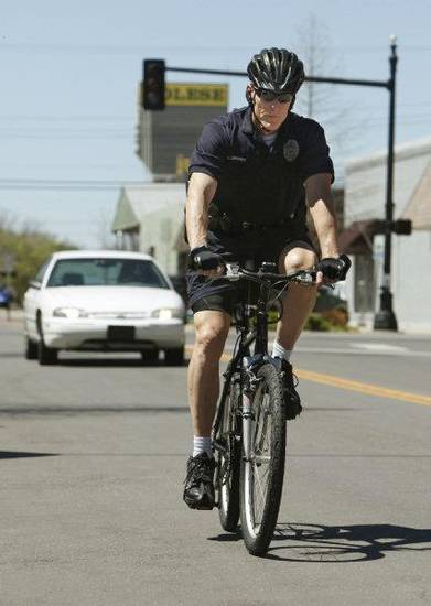 Edmond police Lt. Chuck Linhardt rides his bicycle in downtown Edmond. Linhardt is one of eight bicycle officers who will help promote amendments to Edmond's bicycle ordinance. PHOTO BY PAUL HELLSTERN, THE OKLAHOMAN <strong>PAUL HELLSTERN - THE OKLAHOMAN</strong>