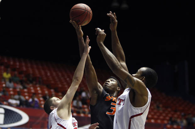 Oklahoma State�s Marcus Smart, center, goes up for the basket against NC State�s players Scott Wood, left, and Lorenzo Brown during a NCAA college basketball game in Bayamon, Puerto Rico, Sunday, Nov. 18, 2012. (AP Photo/Ricardo Arduengo)