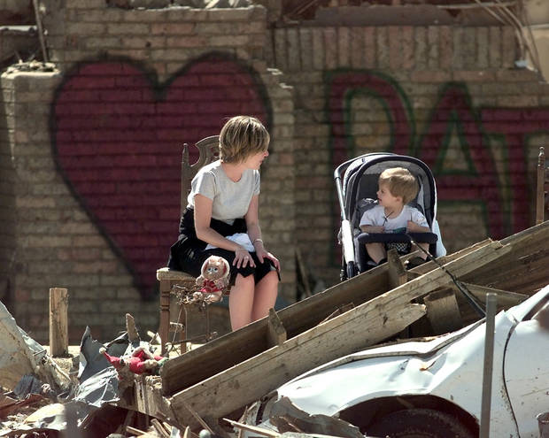 Tornado damage: Lee Harwell and her nephew 20-month-old Gary Patrick-Stice wait in a destroyed house for President Bill Clinton to speak.