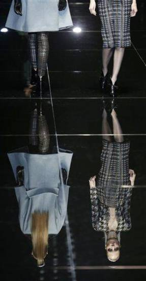 Models are seen reflected on the catwalk as they wear creations for Gucci women's Fall-Winter 2013-14 collection, part of the Milan Fashion Week, unveiled in Milan, Italy, Wednesday, Feb. 20, 2013. (AP Photo/Luca Bruno)