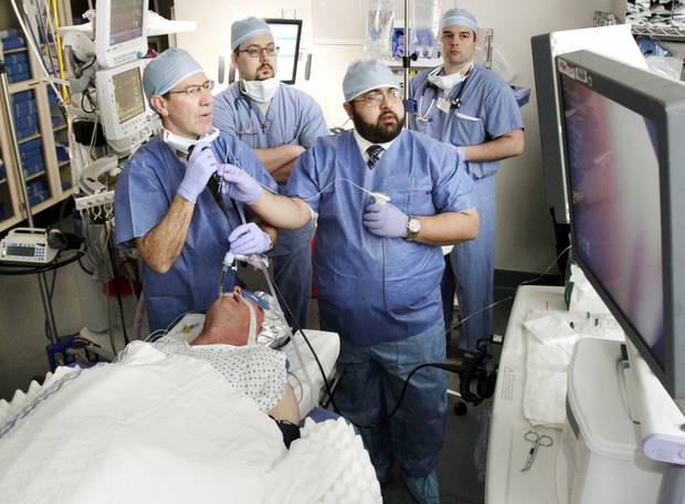 Pulmonologist Brent Brown guides an endoscope through lung passages as Robert Stuemky is treated with the Alair Bronchial Thermoplasty System at the OU Medical Center. Dr. Ahmed Awab assists. <strong>PAUL HELLSTERN</strong>