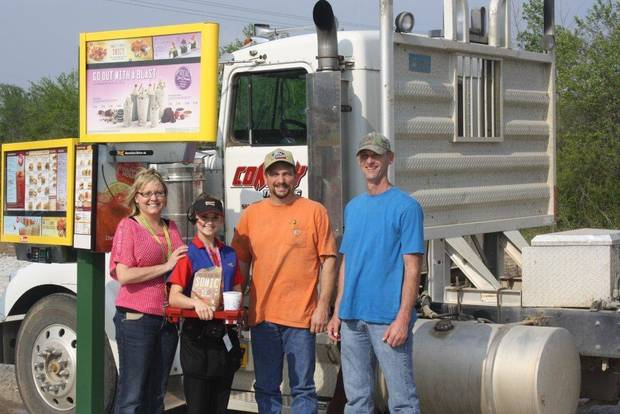 Sonic franchisees Julie Dorries (far left) and Tommy Dorries (far right), along with carhop Halee Elledge (second from left), greet a local guest as he pulls into the first Sonic Drive-In stall built for truck drivers. <strong> - PROVIDED BY SONIC</strong>
