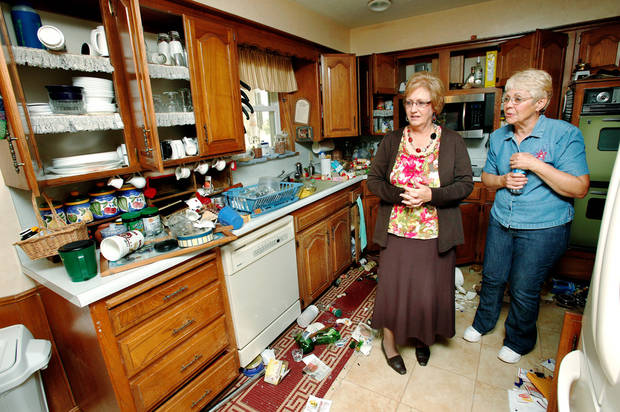 Linda Bloomer, left , looks at the mess created in the kitchen of her friend, Mary Reneau, right,  after a second earthquake shook the Reneau home.  Bloomer and Reneau are in the same Sunday School class at the First Baptist Church in Prague. An eathquake late Saturday night caused extensive damage to the two-story ranch style home of Joseph and Mary Reneau near the community of Sparks in Lincoln County.  Contents inside their home were damaged earlier Saturday when a earthquake was struck the same area.  The Reneaus have lived in their house for 25 years. Photo by Jim Beckel, The Oklahoman  ORG XMIT: KOD