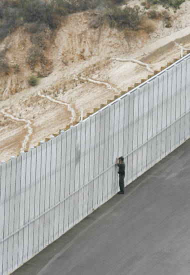 "FILE - In this July 6, 2009 file photo, a U.S. Border Patrol agent peers through a section of fence in San Diego that is part of the ""Smuggler's Gulch"" area along the U.S.-Mexico border. The fence, completed at a cost of $16 million, has helped to seal San Diego's land borders. (AP Photo/Denis Poroy)"