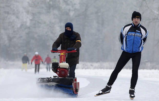 A man clears snow on a frozen pond in Aalter, 75 kilometers (47 miles) west of Brussels, Wednesday, Jan. 23, 2013. Belgium has been in the grip of cold and snowy weather since a week. (AP Photo/Yves Logghe)