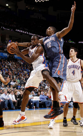 Oklahoma City's Serge Ibaka (9) grabs a rebound beside Charlotte's Tyrus Thomas (12) during an NBA basketball game between the Oklahoma City Thunder and the Charlotte Bobcats at the Oklahoma City Arena, Friday, March 18, 2011. Photo by Bryan Terry, The Oklahoman
