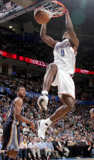 Oklahoma City's Serge Ibaka dunks the ball as Rudy Gay of Memphis watches during the NBA basketball game between the Oklahoma City Thunder and the Memphis Grizzlies at the Ford Center in Oklahoma City on Wednesday, April 14, 2010. 